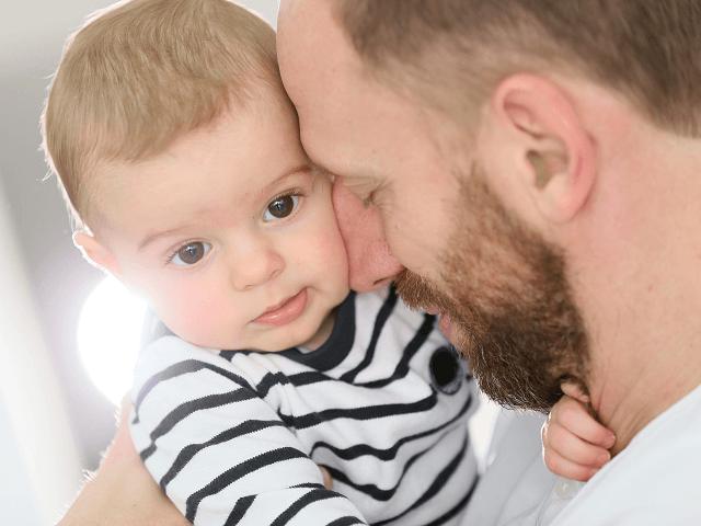 Otecko drží synčeka v náručí