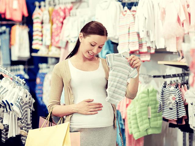 Tehotná žena nakupuje detské oblečenie